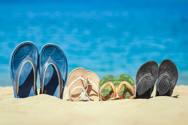 A slippers of the whole family in the sand by the sea on nature while traveling. rest by the water on vacation with shoes.