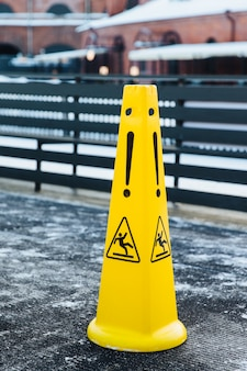 Slippery icon on yellow plastic alerts about hazard on road. caution wet warning sign.