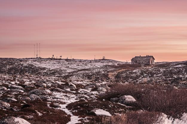 Скользкая дорога к заброшенной метеостанции на холме. суровый полярный вечерний пейзаж. россия.