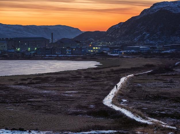 バレンツ海ロシアの海岸にある北極圏の村lodeynoyeへの滑りやすい道 Premium写真