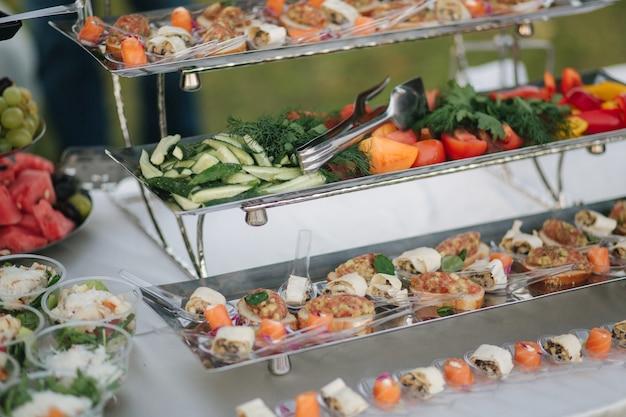얇게 썬 오이와 토마토는 다른 레스토랑 음식 컨셉의 여름 테라스에서 테이블을 제공합니다.
