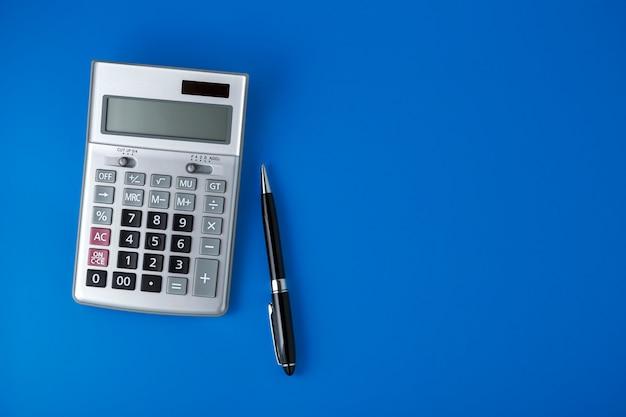 Калькулятор щепки и черная ручка на синем фоне