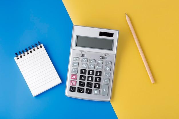 Калькулятор щепки на желто-синем фоне с блокнотом и карандашом