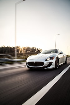 A sliver metallic color sport car driving with high speed on the road.