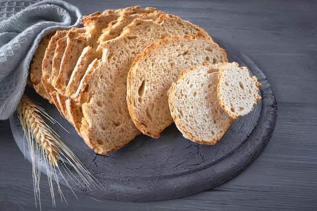 灰色の素朴な木の小麦の耳とスライスした白い丸いパン
