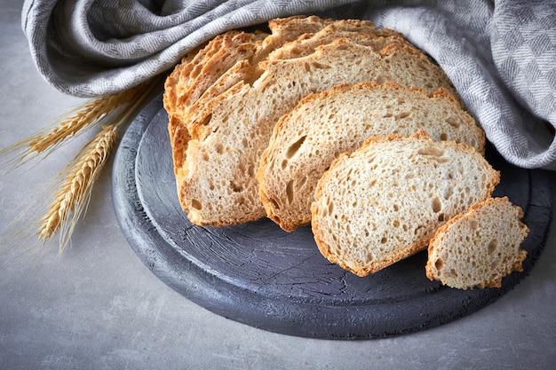 灰色の石の壁に小麦の耳を持つスライスされた白い丸いパン