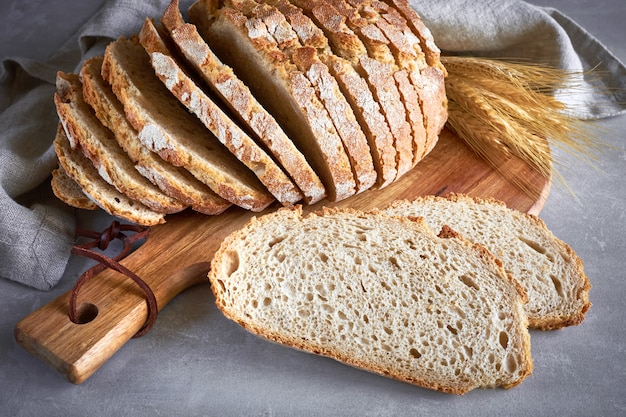 灰色の石の木製のまな板に小麦の穂と白い丸いパンをスライス