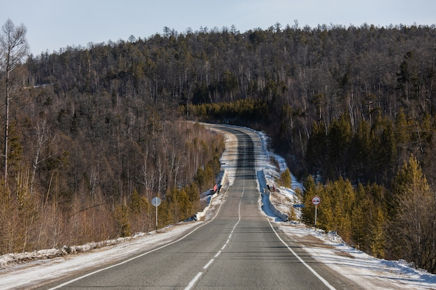 Slope on the empty paved winding road through winter forest on mountain with turns and curve and snow on the roadside.