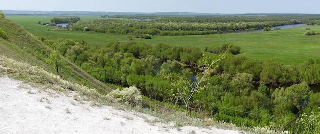 Склон холма долины реки дон в центральной части россии. вид сверху на весенний луг с травой и прудом.