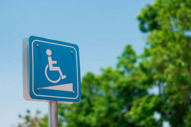 A slope sign for people with disabilities with trees and sky background