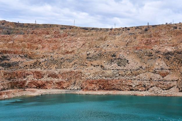Склоны старого известнякового карьера с голубым озером на дне