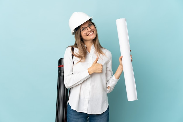 Slovak architect girl holding blueprints isolated on blue background giving a thumbs up gesture