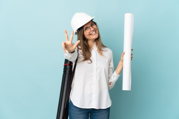 Slovak architect girl holding blueprints isolated on blue background happy and counting three with fingers