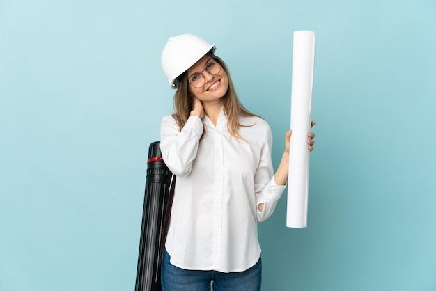 Slovak architect girl holding blueprints isolated on blue background laughing