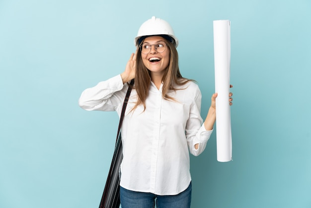 Slovak architect girl holding blueprints isolated on blue background listening to something by putting hand on the ear