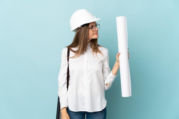 Slovak architect girl holding blueprints isolated on blue background looking to the side
