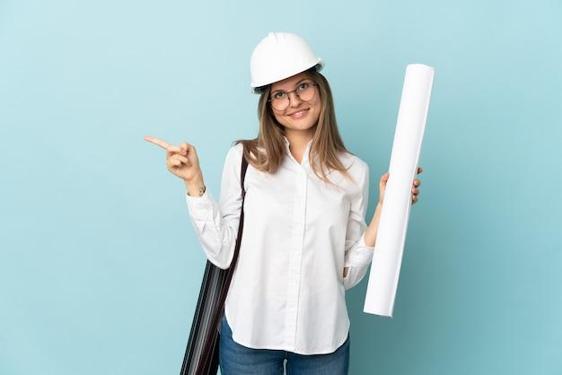 Slovak architect girl holding blueprints isolated on blue background pointing finger to the side