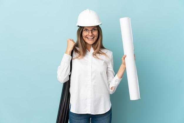 승자 위치에서 승리를 축하하는 파란색 배경에 고립 된 청사진을 들고 슬로바키아어 건축가 소녀