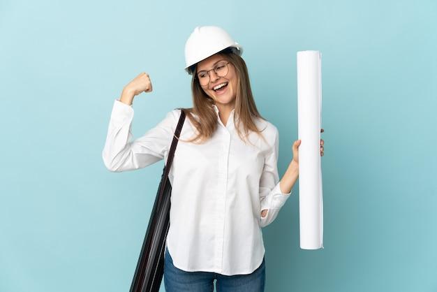 승리를 축하하는 파란색 배경에 고립 된 청사진을 들고 슬로바키아어 건축가 소녀