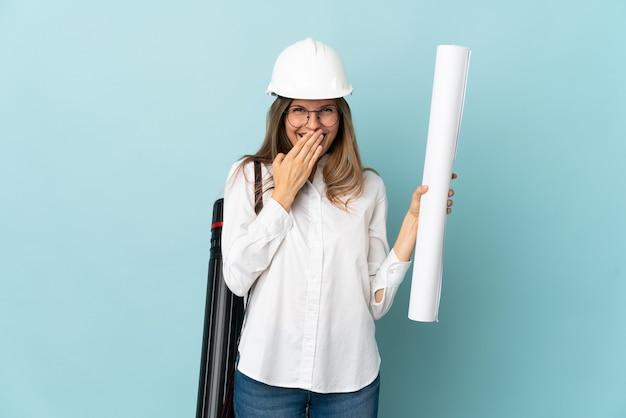 파란색 배경에 행복 하 고 손으로 입 취재 미소에 고립 된 청사진을 들고 슬로바키아어 건축가 소녀