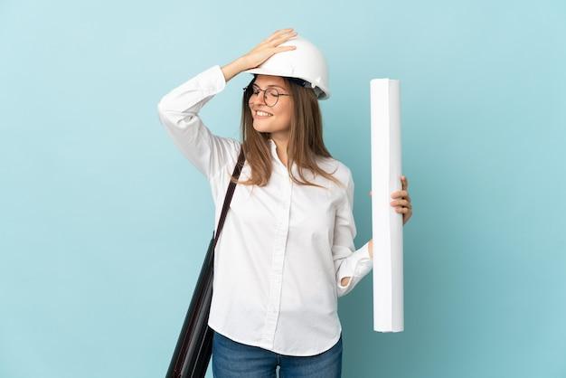 Девушка словацкого архитектора, держащая чертежи, изолированные на синем фоне, кое-что поняла и намеревается найти решение