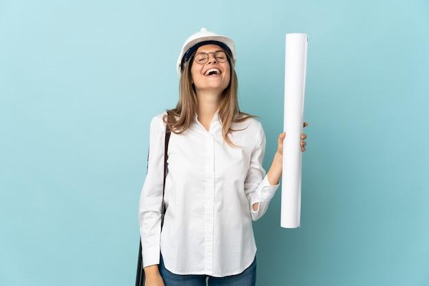 Словацкий архитектор девушка держит чертежи, изолированные на синем фоне смеясь