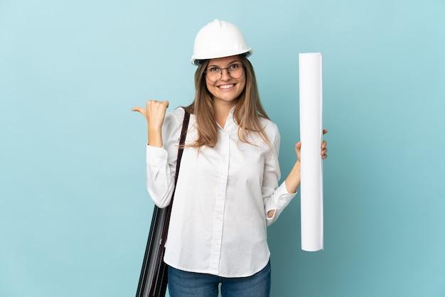 제품을 제시하기 위해 측면을 가리키는 파란색 배경에 고립 된 청사진을 들고 슬로바키아어 건축가 소녀