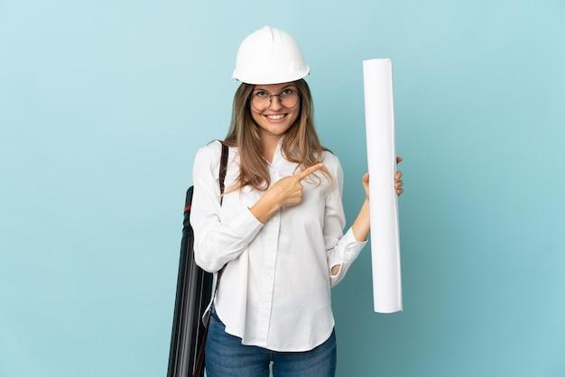 Девушка словацкого архитектора держит чертежи, изолированные на синем фоне, указывая в сторону, чтобы представить продукт