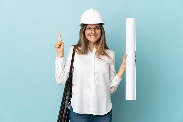 좋은 아이디어를 가리키는 파란색 배경에 고립 된 청사진을 들고 슬로바키아어 건축가 소녀