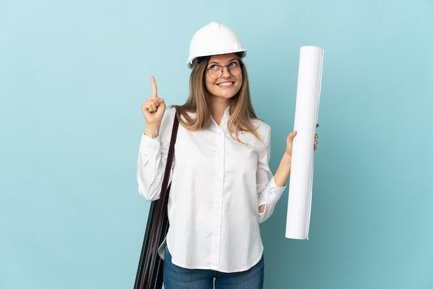 Словацкий архитектор девушка держит чертежи, изолированные на синем фоне, указывая вверх отличную идею