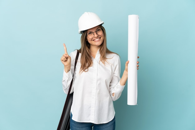파란색 배경에 고립 된 청사진을 들고 슬로바키아어 건축가 소녀는 최고의 기호에 손가락을 들고