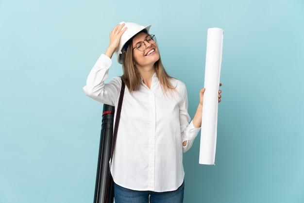 Словацкий архитектор девушка держит чертежи, изолированные на синем фоне, много улыбаясь