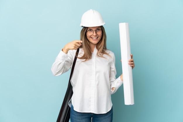 파란색 배경 놀라게 하 고 앞을 가리키는에 고립 된 청사진을 들고 슬로바키아어 건축가 소녀