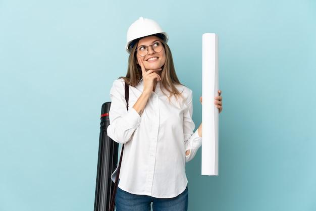 찾고있는 동안 아이디어를 생각하는 파란색 배경에 고립 된 청사진을 들고 슬로바키아어 건축가 소녀