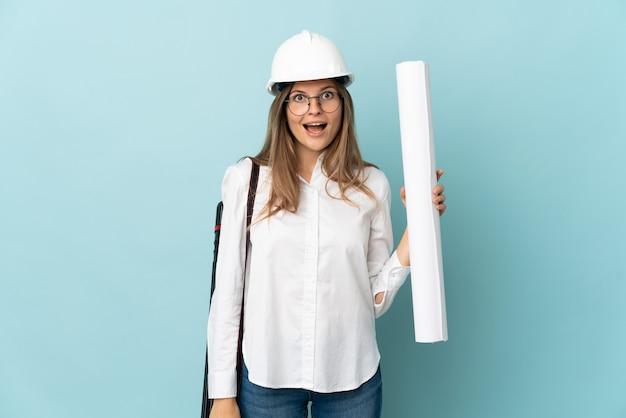 깜짝 표정으로 파란색 배경에 고립 된 청사진을 들고 슬로바키아어 건축가 소녀