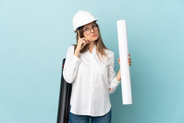 Словацкий архитектор девушка держит чертежи, изолированные на синей стене, думая об идее