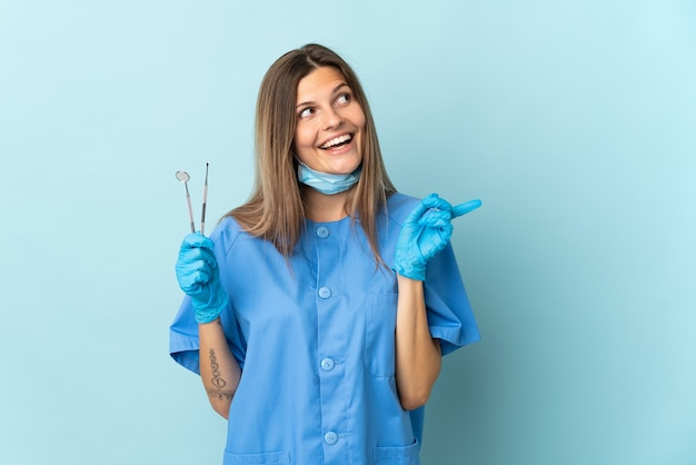 Slovak dentist holding tools isolated on blue background intending to realizes the solution while lifting a finger up