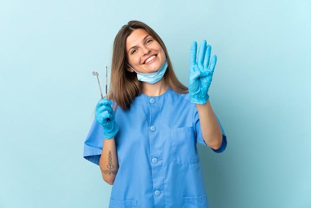 幸せな青い背景に分離されたツールを保持し、指で4を数えるスロバキアの歯科医