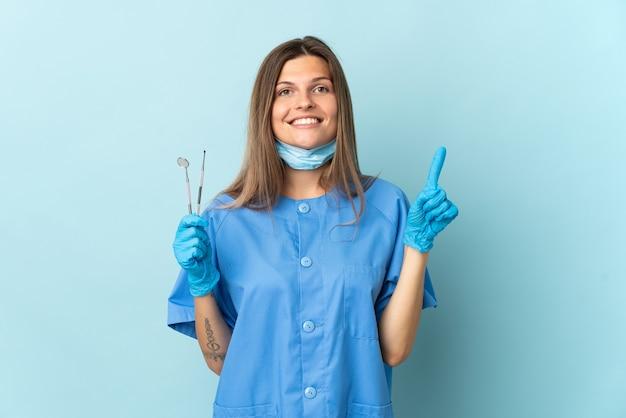 素晴らしいアイデアを指している青い背景に分離されたツールを保持しているスロバキアの歯科医