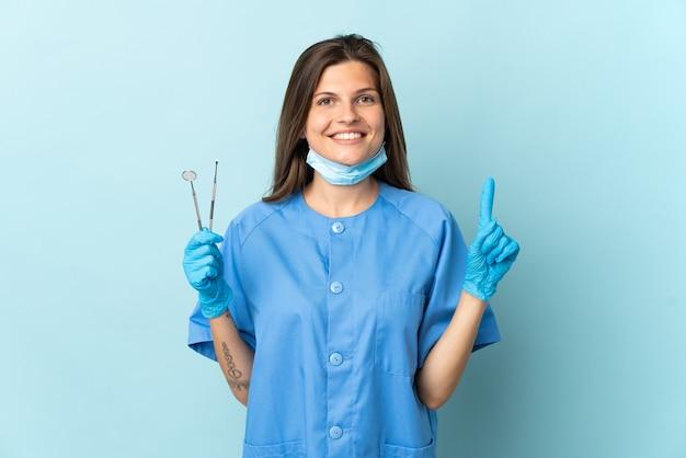 最高の兆候を示し、指を持ち上げて青い背景で隔離のツールを保持しているスロバキアの歯科医