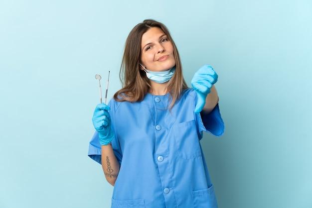 否定的な表現で親指を示す青い背景に分離されたツールを保持しているスロバキアの歯科医