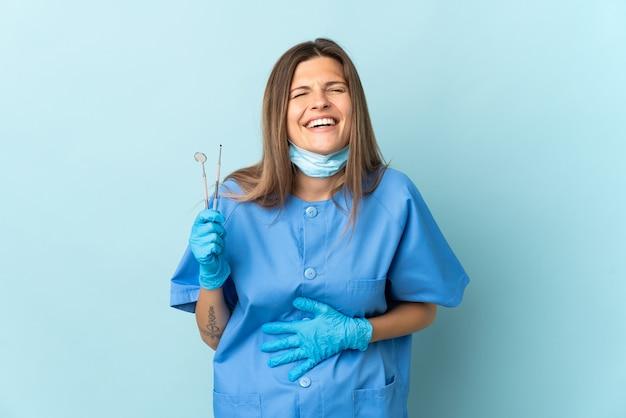Словацкий дантист держит инструменты, изолированные на синем фоне, много улыбаясь