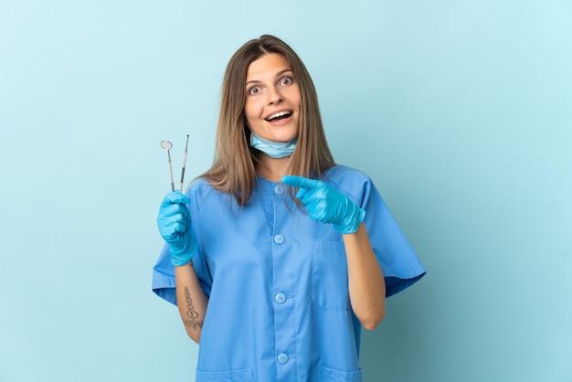 青い背景に分離されたツールを保持しているスロバキアの歯科医は驚いて正面を指しています