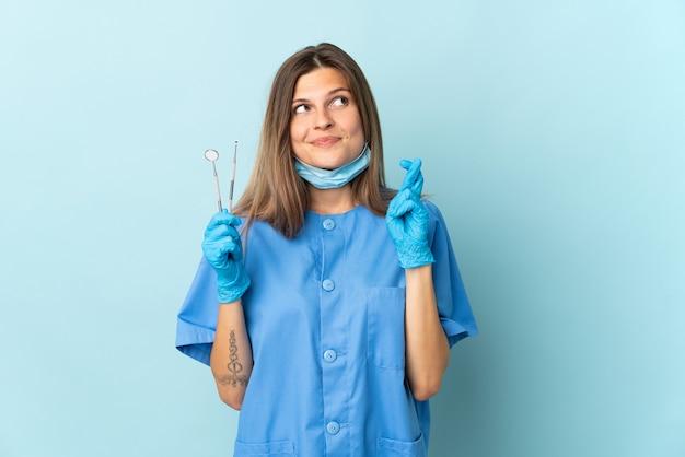 指が交差し、最高を願って青い背景に分離されたツールを保持しているスロバキアの歯科医