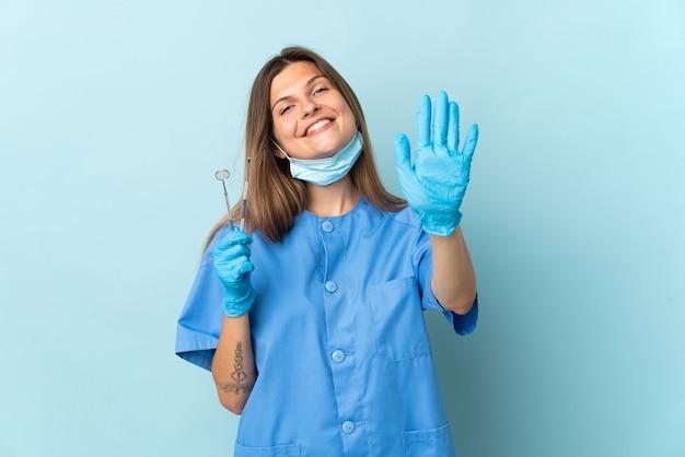 指で5を数える青い壁に分離されたツールを保持しているスロバキアの歯科医