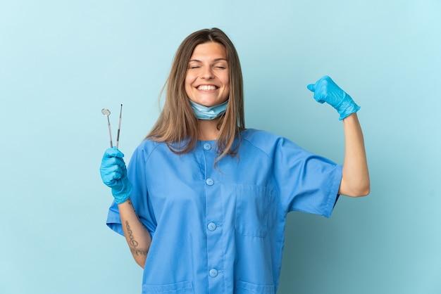 Словацкий дантист держит инструменты, изолированные на синей стене, делает сильный жест