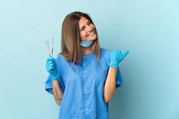 製品を提示する側を指している青い壁に分離されたツールを保持しているスロバキアの歯科医