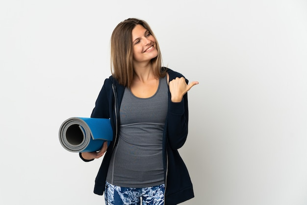 제품을 제시하기 위해 측면을 가리키는 흰색 배경에 고립 된 요가 수업에가는 슬로바키아어 소녀
