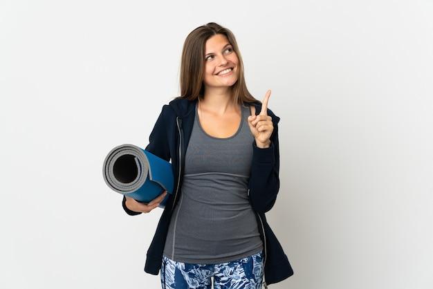 멋진 아이디어를 가리키는 흰색 배경에 격리된 요가 수업에 가는 슬로바키아 소녀 프리미엄 사진