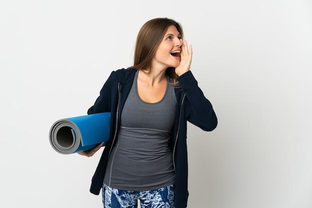 Словацкая девушка идет на занятия йогой, изолированные на белом фоне, кричит с широко открытым ртом в сторону